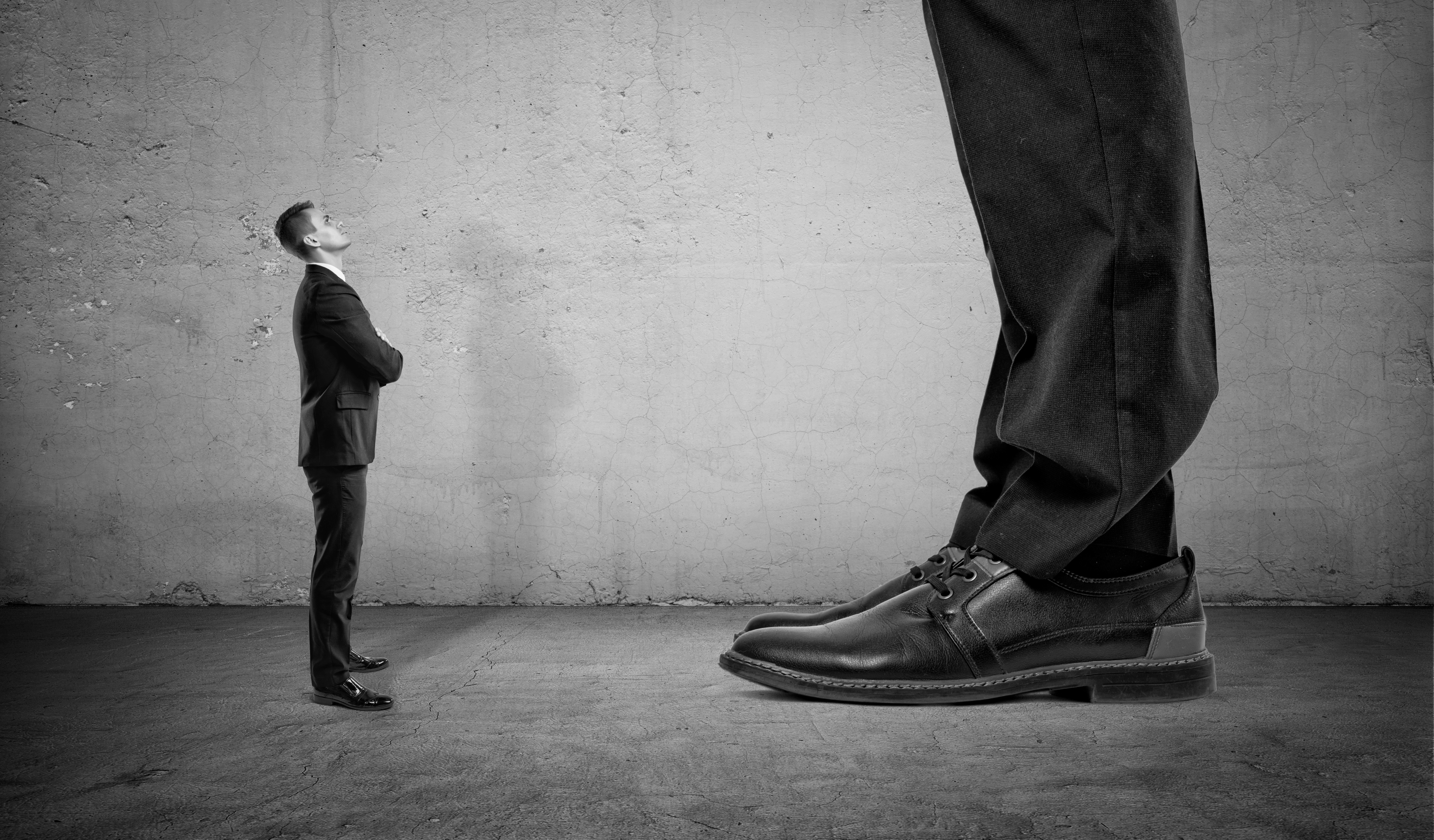 Tiny businessman looking up on huge legs of another man